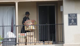 A young man retrieves food supplies left by the North Texas Food Bank and the Red Cross on the front stoop of an apartment at The Ivy Apartments complex, Thursday, Oct. 2, 2014, in Dallas, where Thomas Eric Duncan, the Ebola patient who traveled from Liberia to Dallas last week, was staying.  Dallas County officials have ordered family members who had contact Duncan, quarantined in their home to prevent the spread of disease. (AP Photo/The Dallas Morning News, David Woo)