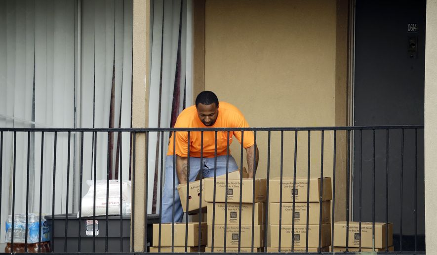 Representatives of the North Texas Food Bank deliver food items to a unit at The Ivy Apartments Complex, Thursday, Oct. 2, 2014, in Dallas. Dallas County officials have ordered family members who had contact with the patient diagnosed with the Ebola virus to stay inside their home. (AP Photo/Tony Gutierrez)