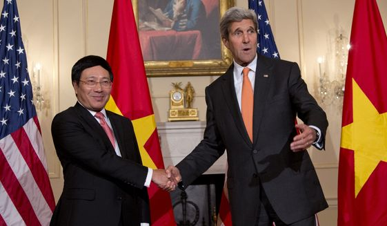Secretary of State John Kerry shakes hands with Vietnamese Foreign Minister Pham Binh Minh as they speak to media at the State Department in Washington, Thursday, Oct. 2, 2014, before having a working lunch. (AP Photo/Carolyn Kaster)