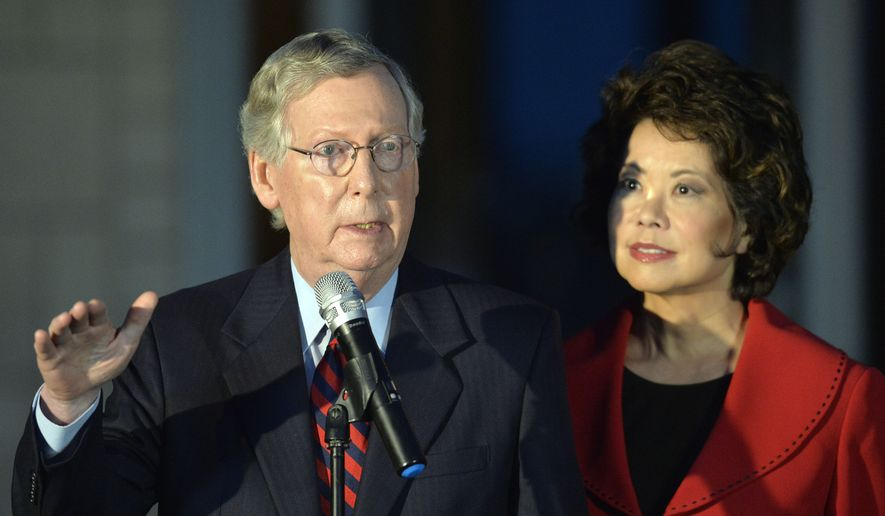 Kentucky Sen. Mitch McConnell, left, addresses the media as his wife Elaine Chao looks on Thursday, Oct. 2, 2014, at Donamire Farm in Lexington, Ky. McConnell was in Kentucky to attend a fundraiser, and to receive an endorsement from former Massachusetts Gov. Mitt Romney for his re-election bid to the senate.  (AP Photo/Timothy D. Easley)