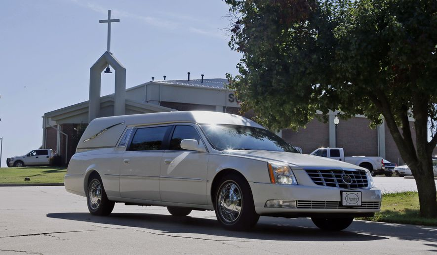 The casket of Colleen Hufford is driven away from Southgate Baptist Church following funeral services in Moore, Okla., Friday, Oct. 3, 2014. Colleen Hufford was killed in a workplace violence incident on Sept. 25. (AP Photo/Sue Ogrocki)