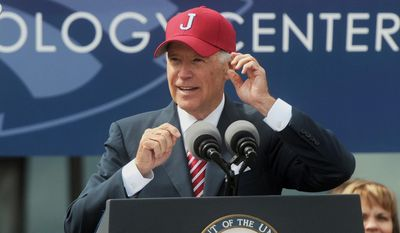 Vice President Joe Biden dons a Joplin High School baseball cap during a dedication ceremony for a combined high school and vocational school that replaces one destroyed by a deadly tornado more than three years ago, Friday, Oct. 3, 2014, in Joplin, Mo. (AP Photo/The Joplin Globe, Laurie Sisk)