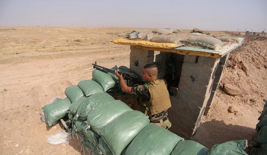 In this Thursday, Oct. 2, 2014 photo, an Iraqi Shiite militiamen takes cover after clashes with militants from the Islamic State group, near Qara Tappa, about 75 miles northeast of Baghdad in Iraq's Diyala province. (AP Photo/Jaber al-Helo)