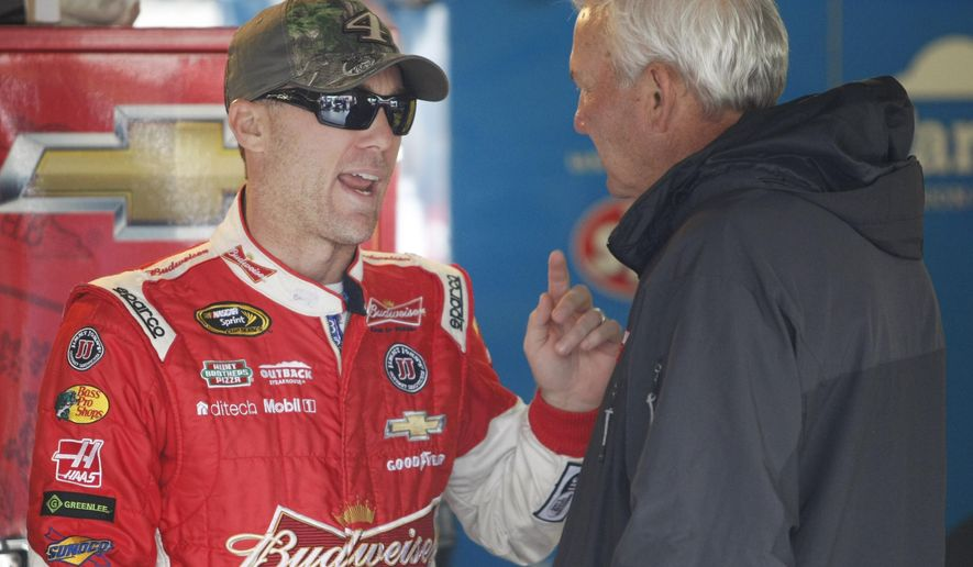 NASCAR driver Kevin Harvick talks with sports commentator and former race driver Dale Jarrett in the garage at Kansas Speedway in Kansas City, Kan., Friday, Oct. 3, 2014. (AP Photo/Colin E. Braley)