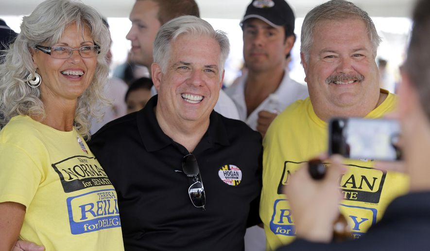 FILE - In this July 16, 2014, file photo, Maryland Republican gubernatorial candidate Larry Hogan, center, poses for a picture at the 38th Annual J. Millard Tawes Crab and Clam Bake in Crisfield, Md.  Hogan and Maryland Democratic gubernatorial candidate, Lt. Gov. Anthony Brown have not provided a look into their personal finances after repeated requests to their campaigns by The Associated Press for more than two months to view their tax returns.  Candidates are not required by law to make tax returns public. However, candidates in other states often have made at least some of their returns available for review in a gesture of transparency. (AP Photo/Patrick Semansky, File)