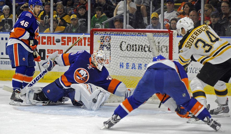 New York Islanders goalie Chad Johnson (30) makes a save on Boston Bruins center Carl Soderberg (34), of Sweden, during the first period of a preseason NHL hockey game in Bridgeport, Conn., on Friday, Oct. 3, 2014. (AP Photo/Fred Beckham)