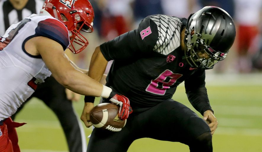 Arizona's Scooby Wright III, left, strips the ball from Oregon's Marcus Mariota during the 4th quarter during a NCAA Collage Football game in Eugene, Oregon Thursday Oct 2, 2014. (AP Photo/The Register-Guard)