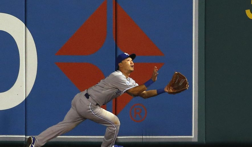 Kansas City Royals right fielder Norichika Aoki, of Japan, catches a fly ball hit by Los Angeles Angels' C.J. Cron during the eighth inning of Game 1 of baseball's AL Division Series in Anaheim, Calif., Thursday, Oct. 2, 2014. (AP Photo/Lenny Ignelzi)