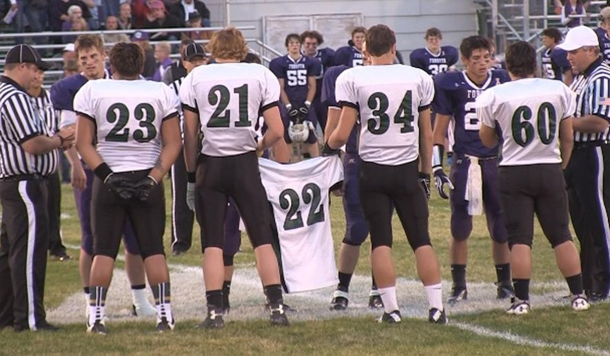 In this photo taken on Sept. 26, 2014, Colstrip captains, from left, Mikah Little Axe, Rodney Studiner, Tritan Aberle and Wyatt Anzalone carry Dallen Walker's jersey to midfield to meet with officials and the Forsyth captains before a high school football game in Forsythe, Mont.(AP Photo/The Billings Gazette, Slim Kimmel)
