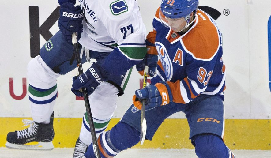 Vancouver Canucks' Alexander Edler (23) and Edmonton Oilers' Ryan Nugent-Hopkins (93) vie for the puck during the third period of a preseason NHL hockey hockey game Thursday, Oct. 2, 2014, in Edmonton, Alberta. (AP Photo/The Canadian Press, Jason Franson)