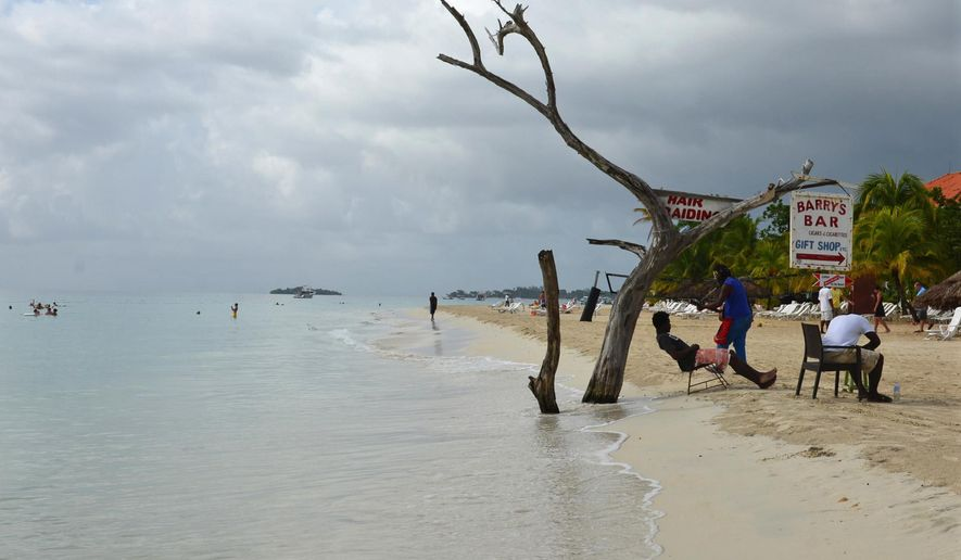 In this Sept. 14, 2014 photo, the tide gnaws away at a badly eroding patch of resort-lined beach in Negril in western Jamaica. The shrinking coastline long has raised worry for the region's environmental and economic future. Now, the erosion is expected to worsen as a result of climate change, and a hint of panic is creeping through this laid back village, one of the top destinations in a country where a quarter of all jobs depend on tourism. (AP Photo/David McFadden)