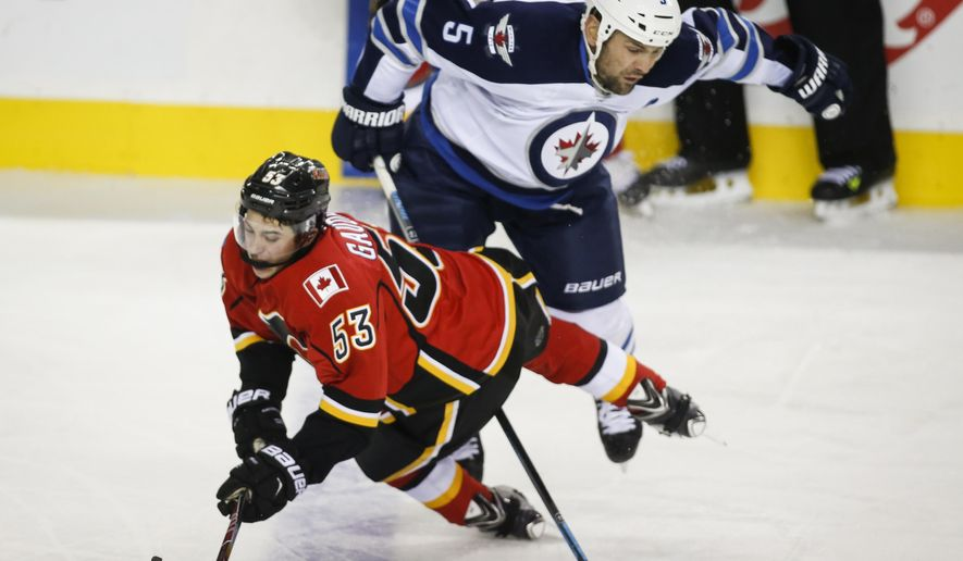 Winnipeg Jets' Mark Stuart, right, knocks Calgary Flames' Johnny Gaudreau to the ice during the third period of an NHL pre-season hockey game, Thursday, Oct. 2, 2014 in Calgary. (AP Photo/The Canadian Press, Jeff McIntosh)