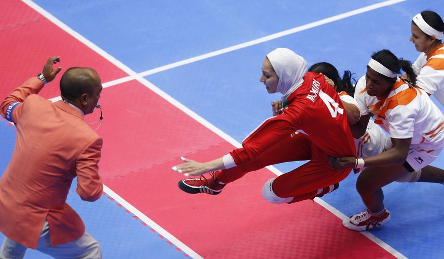 Iran's Malihe Miri, red jersey, is caught by India's team at the women's team Kabaddi gold medal match at the 17th Asian Games in Incheon, South Korea, Friday, Oct. 3, 2014.  (AP Photo/Kin Cheung)