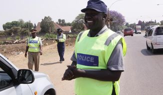 """A police officer smiles after stopping a vehicle in Harare, Friday, Oct. 3, 2014 on World Smile Day.  According to  Zimbabwe's deputy Minster of Home Affairs Ziyambi Ziyambi whose ministry is in charge of the police, the hospitality agency would conduct """"smiling""""  training sessions to make the law enforcers friendlier towards tourists and motorists. (AP Photo/Tsvangirayi Mukwazhi)"""