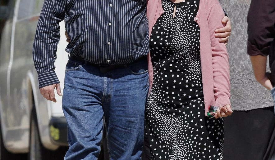 K.C. Hufford, left, the widower of Colleen Hufford, walks with an unidentified mourner before the start of the funeral for Colleen Hufford at Southgate Baptist Church in Moore, Okla., Friday, Oct. 3, 2014. Colleen Hufford was killed in a workplace violence incident on Sept. 25. (AP Photo/Sue Ogrocki)