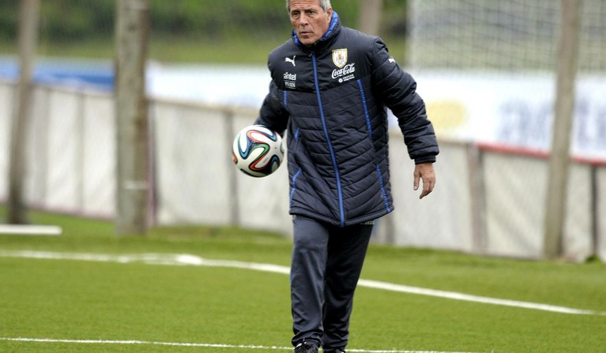 FILE - In this May 21, 2004 file photo, Uruguay's coach Oscar Tabarez leads a training session on the outskirts of Montevideo, Uruguay. Tabarez signed a contract on Friday, Oct. 3, 2014 to continue coaching Uruguay's national team for the next four years. (AP Photo/Matilde Campodonico, File)