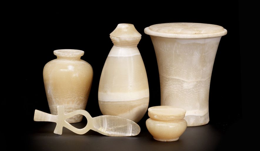 In this photo provided by Bonhams Auctioneers are banded travertine objects: from front left: a cosmetic spoon with the handle in the form of an ankh-sign and a small 'magical jar' vase with a stopper. From left, rear: a bag-shaped flask; a kohl-pot; and a cosmetic vase with lid, all part of Treasure of Harageh collection. The Metropolitan Museum of Art in New York has purchased the objects, part of a collection of 37, 4,000-year-old Egyptian artifacts found a century ago by a British explorer, averting a plan to auction the antiquities that had drawn criticism from historians. (AP Photo/Bonhams Auctioneers)