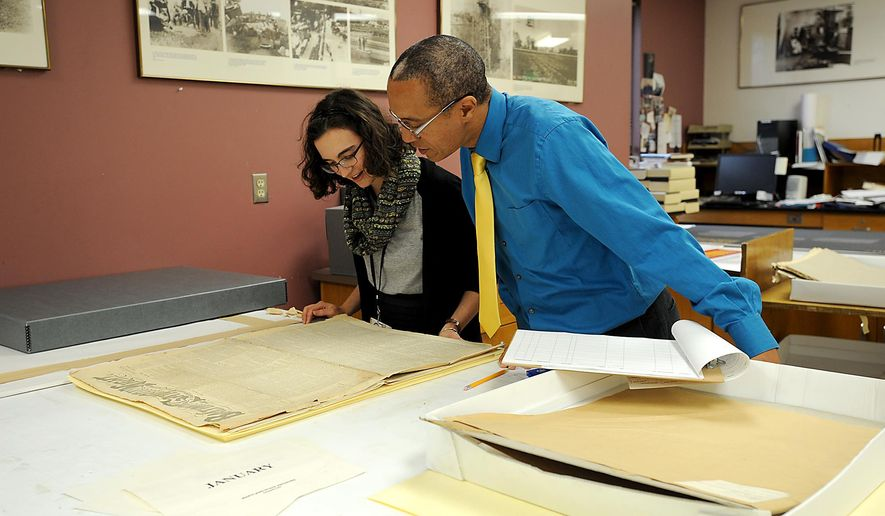 In this photo taken on Wednesday, Oct. 1, 2014. special collections intern Hannah Strum and Chris Haley, Director of the Study of the Legacy of Slavery in Maryland, work on conserving a Baltimore newspaper from the 1870's at The Maryland State Archives in Annapolis, Md.  The archive is hosting a first-ever open house Saturday. (AP Photo/Capital Gazette, Paul W. Gillespie) MAGS OUT, NO SALES, TV OUT
