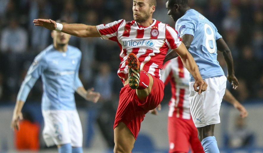 Olympiacos Pajtim Kasami, center, heads the ball in front of Malmo's Enoch Adu, right, during their Champions League group A football match Malmo FF vs. Olympiacos FC in Malmo, Sweden Wednesday, Oct. 1, 2014. (AP Photo/TT, Andreas Hillergren)   SWEDEN OUT
