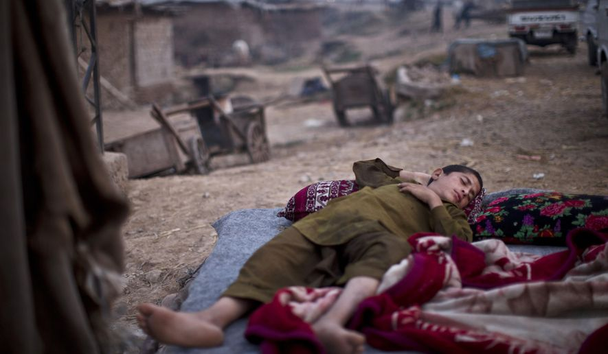 A Pakistani youth, who was displaced with his family from Pakistan's tribal region of Mohmand Agency due to fighting between the Taliban and the army, sleeps on the ground near his family's makeshift home on the outskirts of Islamabad, Pakistan, early Friday, Oct. 3, 2014. (AP Photo/Muhammed Muheisen)
