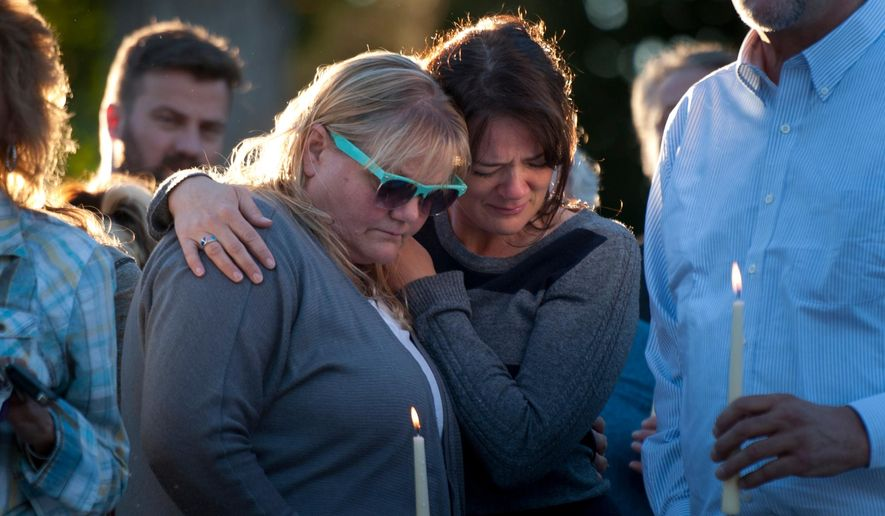 In this photo taken on Thursday, Oct. 2, 2014, family and friends console one each other while people speak and tell stories during a vigil for the Strack family at Pioneer Park in Provo, Utah. More than 100 family members and friends gathered to remember five members of the family mysteriously found dead at home last weekend. (AP Photo/The Daily Herald, Grant Hindsley) MANDATORY CREDIT