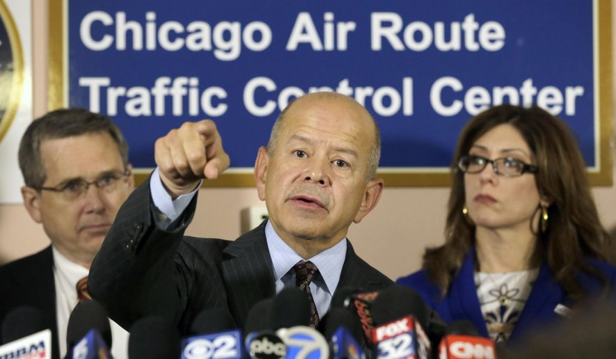Federal Aviation Administration Administrator Michael Huerta, center, addresses the media after touring the Chicago Air Route Traffic Control Center with U.S. Sen. Mark Kirk R-Ill., left, and Rosemarie S. Andolino Commissioner, Chicago Department of Aviation, Friday, Oct. 3, 2014, in Aurora , Ill. Lawmakers have called for an investigation into how a former contract employee entered the center, which was sabotaged by a fire that shut down Chicago's two international airports. (AP Photo/Charles Rex Arbogast)