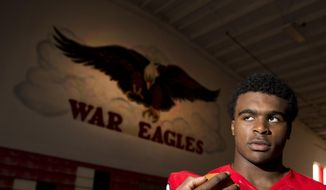In this Friday, Sept. 26, 2014, photo, Woodward Academy running back Elijah Holyfield, son of five-time boxing champion Evander Holyfield poses for a portrait in College Park,, Ga. Colleges from Oregon to Ohio State to Georgia are taking notice, especially after the young Holyfield started off his season with a seven-touchdown game. (AP Photo/John Bazemore)