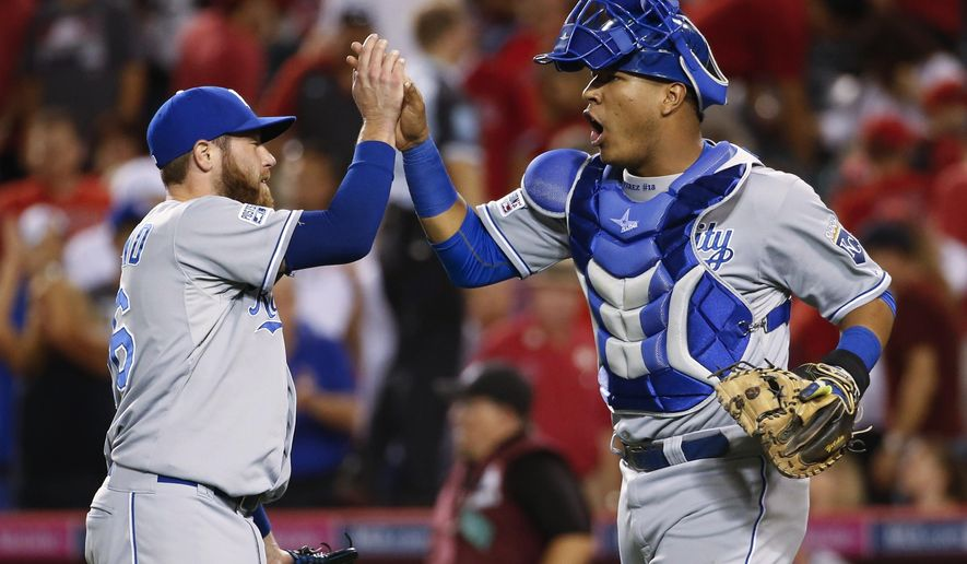 Kansas City Royals catcher Salvador Perez, right, celebrates with relief pitcher Greg Holland after the Royals defeated the Los Angeles Angels 3-2 in 11 innings in Game 1 of baseball's AL Division Series in Anaheim, Calif., Thursday, Oct. 2, 2014. (AP Photo/Lenny Ignelzi)