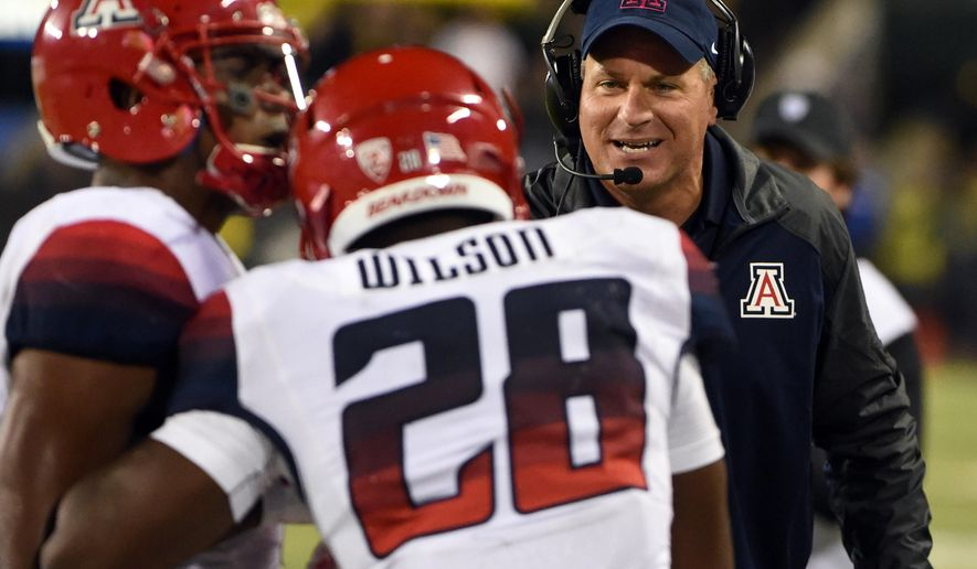 Arizona head coach Rich Rodriguez celebrates with running back Nick Wilson (28) after Wilson scored a touchdown during the third quarter of the NCAA college football game against Oregon at Autzen Stadium on Thursday, Oct. 2, 2014, in Eugene, Ore. Arizona won the game 31-24. (AP Photo/Steve Dykes)