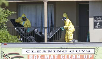 Hazardous material cleaners prepare to hang black plastic outside the apartment in Dallas, Friday, Oct. 3, 2014, where Thomas Eric Duncan, the Ebola patient who traveled from Liberia to Dallas stayed last week. The family living there has been confined under armed guard while being monitored by health officials. (AP Photo/LM Otero)
