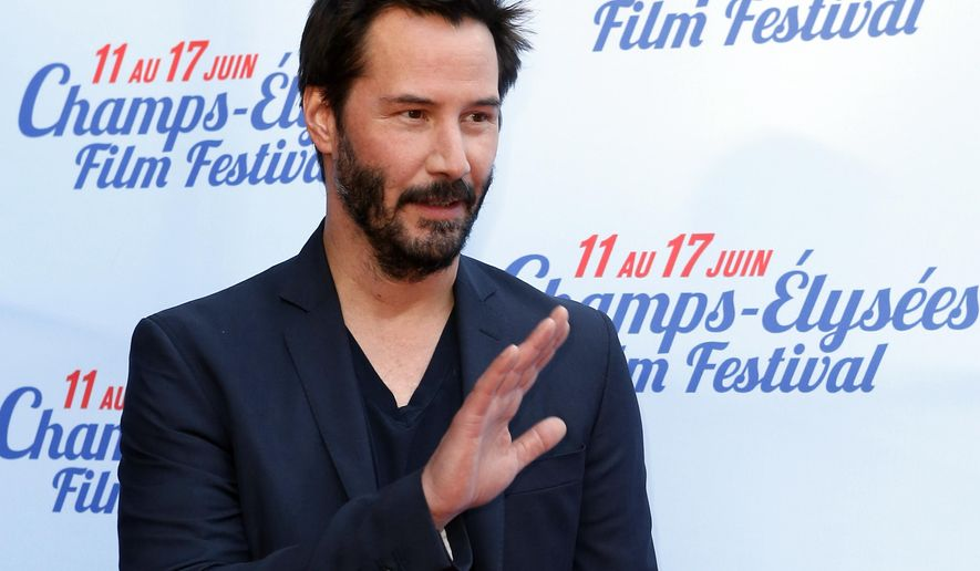 """FILE - In this June 14, 2014 file photo, Keanu Reeves waves at the screening of the film """"Side by Side"""" during the Champs-Elysees Film Festival, in Paris. A Los Angeles Superior Court judge on Thursday, Oct. 2, 2014, ordered a 50-year-old Michigan woman to stay away from Reeves and his home after she was detained at the property last month. Court filings state the woman, Kerry Raus, swam in the actor's pool and took a shower in Reeves' home on Sept. 15, 2014, before she was spotted and taken into custody. (AP Photo/Jacques Brinon, file)"""