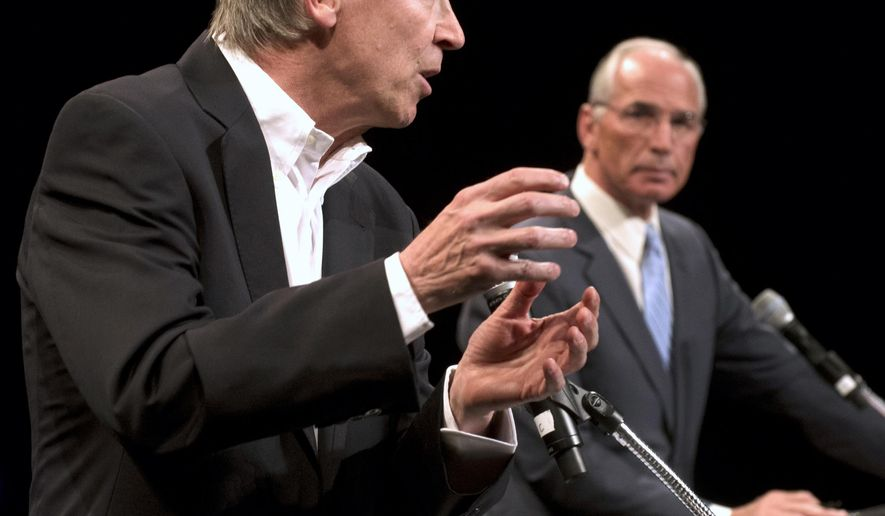 John Hickenlooper, left, makes a point while opponent Bob Beauprez listens during a gubernatorial debate at Memorial Hall in Pueblo, Colo., Thursday Oct. 2, 2014. (AP Photo/The Pueblo Chieftain, Chris Mclean)