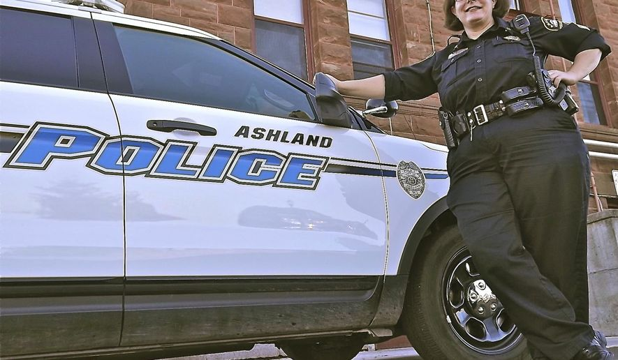 ADVANCE FOR USE MONDAY, OCT. 6 - In this photo taken on Sept. 26, 2014, Ashland Police Sgt. Michelle Tutor poses outside the Ashland, Wis.,  Police Department. The Wisconsin Association of Women Police recently named Tutor as Wisconsin Woman Police Officer of the year.  (AP Photo/The Ashland Daily Press, Rick Olivo)