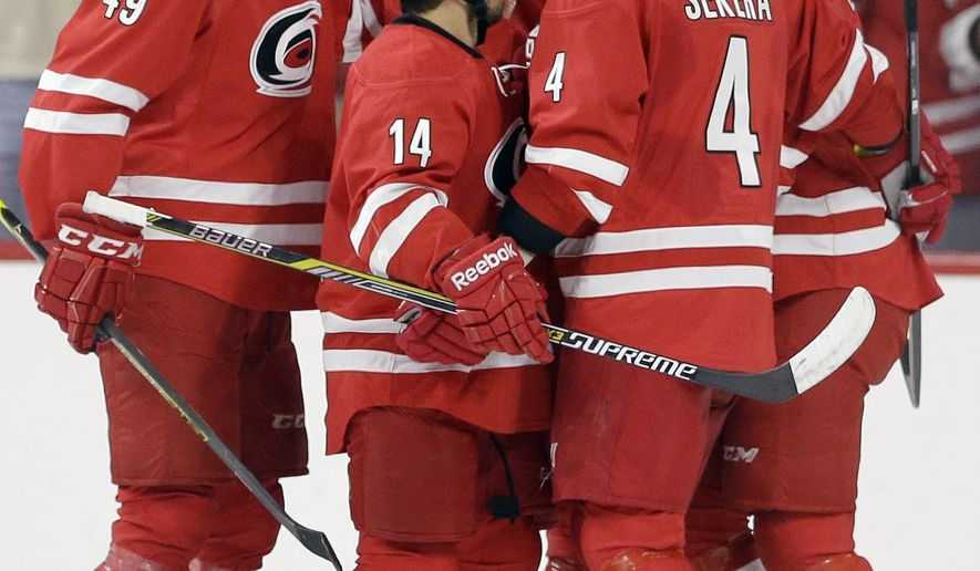 Carolina Hurricanes' Victor Rask (49), Nathan Gerbe (14) Justin Faulk (27), Andrej Sekera (4) and Elias Lindholm (16), of Sweden, celebrate Lindholm's goal against the Buffalo Sabres during the second period of a preseason NHL hockey game in Raleigh, N.C., Friday, Oct. 3, 2014. (AP Photo/Gerry Broome)