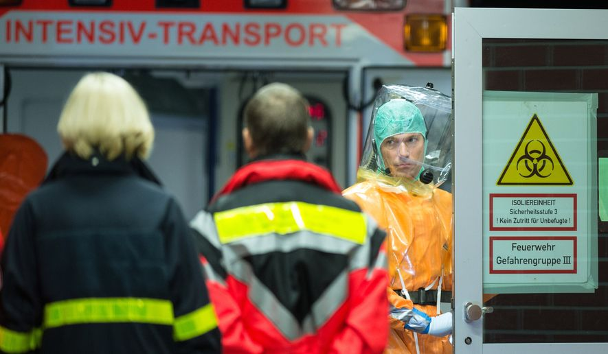A Ugandan doctor who contracted Ebola while working in Sierra Leone is being brought in a special ambulance, background, to the quarantine ward of the University clinic in Frankfurt, central Germany, early Friday, Oct. 3, 2014. Authorities in the German state of Hesse say the doctor, who was not identified, had worked for an Italian aid group in West Africa when he became infected. (AP Photo/dpa, Boris Roessler)
