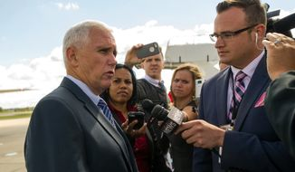 Indiana Gov. Mike Pence talks to the media about the conversation he had with President Barack Obama on the tarmac at Tri-State Aero at Evansville Regional Airport, Friday, Oct. 3, 2014, in Evansville, Ind. (AP Photo/Daniel R. Patmore)