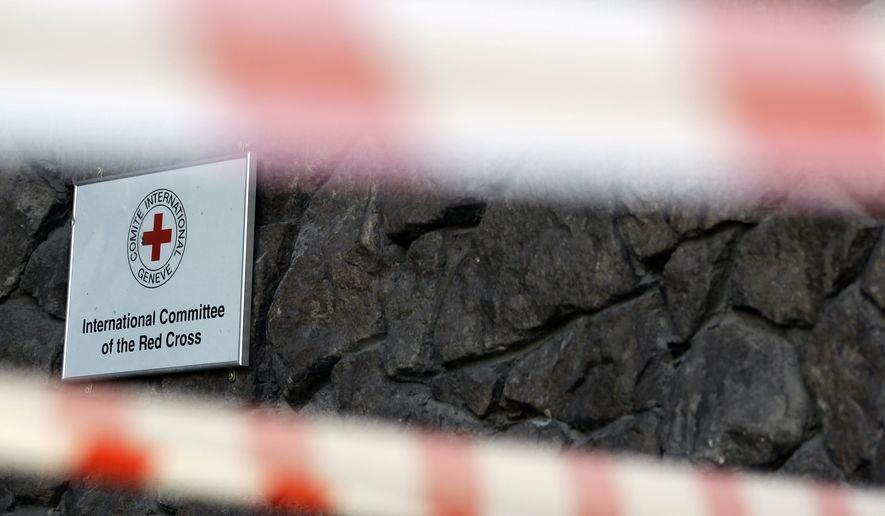A damaged sign on a Red Cross office is seen behind police tape after shelling, in the town of Donetsk, eastern Ukraine, Friday, Oct. 3, 2014. A Red Cross staffer died Thursday when a shell landed near the group's office in Donetsk. (AP Photo/Darko Vojinovic)