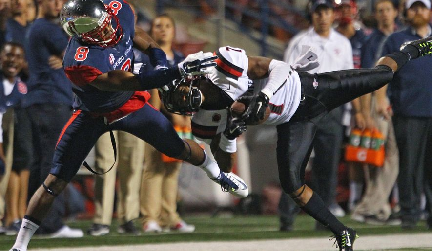 San Diego State's J.J. Whittaker intercepts a pass to Fresno State's Da'Mari Scott during the first half of an NCAA college football game in Fresno, Calif., Friday, Oct. 3, 2014. (AP Photo/Gary Kazanjian)