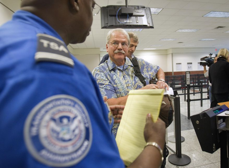 FILE - In this Oct. 4, 2011 file photo, passenger Don Heim, right, of Alpharetta, Ga., is briefed by Transportation Security Administration trainer Byron Gibson before going through a new expedited security line at Hartsfield-Jackson International Airport in Atlanta.  The news that a man flew from Liberia to the U.S. after exposure to Ebola, and wound up in a hospital isolation ward, has led to calls for tougher measures to protect Americans, such as a ban on flights from countries hit by the epidemic. Federal health officials and airlines have dismissed any risk to passengers who flew with the man last month and say they are protecting travelers by screening passengers and wiping down airplane cabins nightly.  (AP Photo/David Goldman)