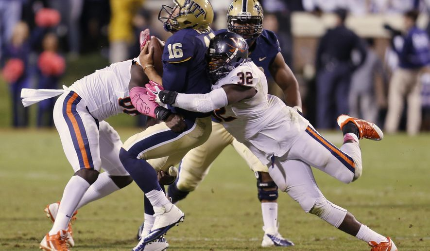 Pittsburgh quarterback Chad Voytik (16) is hit by Virginia linebacker Max Valles, left, and defensive end Mike Moore (32) during the first half of an NCAA college football game in Charlottesville, VA., Saturday, Oct. 4, 2014.  (AP Photo/Steve Helber)