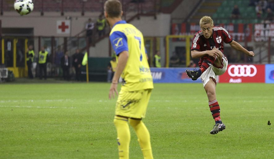 AC Milan's Keisuke Honda scores on a free-kick his side's second goal, during the Serie A soccer match between AC Milan and Chievo Verona at the San Siro stadium in Milan, Italy, Saturday, Oct. 4, 2014. (AP Photo/Antonio Calanni)