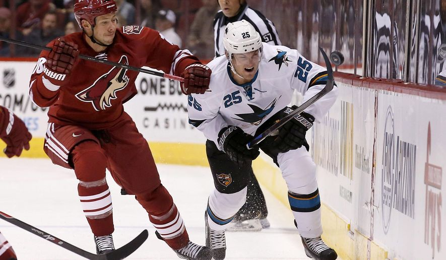 San Jose Sharks' Tye McGinn (25) tries to control the puck in front of Arizona Coyotes' David Moss (18) during the first period of a preseason NHL hockey game Friday, Oct. 3, 2014, in Glendale, Ariz. (AP Photo/Ross D. Franklin)