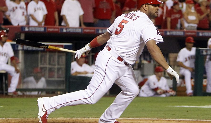 Los Angeles Angels' Albert Pujols drops his bat after he hit an RBI single against the Kansas City Royals in the sixth inning of Game 2 of baseball's AL Division Series in Anaheim, Calif., Friday, Oct. 3, 2014. (AP Photo/Gregory Bull)
