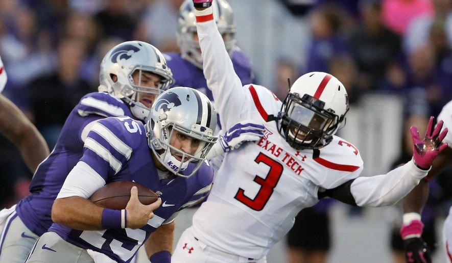 Kansas State quarterback Jake Waters (15) runs past Texas Tech defensive back J.J. Gaines (3) during the first half of an NCAA college football game in Manhattan, Kan., Saturday, Oct. 4, 2014. Kansas State wide receiver Kody Cook, back, blocks on the play. (AP Photo/Orlin Wagner)