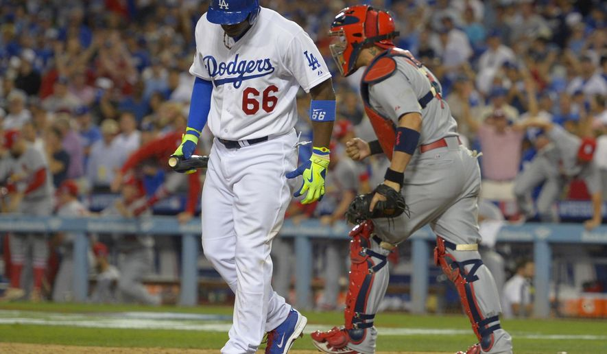Los Angeles Dodgers' Yasiel Puig, left, walks away from the plate after striking out as St. Louis Cardinals catcher Yadier Molina, right, reacts in the ninth inning to end Game 1 of baseball's NL Division Series in Los Angeles, Friday, Oct. 3, 2014. The Cardinals won 10-9. (AP Photo/Mark J. Terrill)