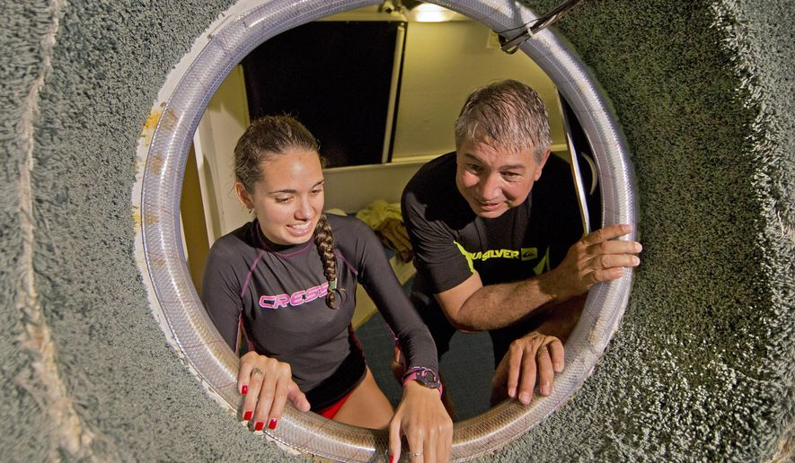 """In this photo provided by the Florida Keys News Bureau, Roane State Community College adjunct professor Jessica Fain, 25, left, and associate professor Bruce Cantrell, 63, enter the Jules Undersea Lodge habitat to begin a 73-day """"Classroom Under the Sea"""" project Friday, Oct. 3, 2014, 25 feet beneath the surface of a Florida Keys lagoon in Key Largo, Fla. Besides teaching weekly online marine science classes, via YouTube, the Tennessee instructors hope to break a record for underwater habitation currently held by Rick Presley when he resided at Jules for 69 days and 19 minutes in 1992. (AP Photo/Florida Keys News Bureau, Bob Care)"""