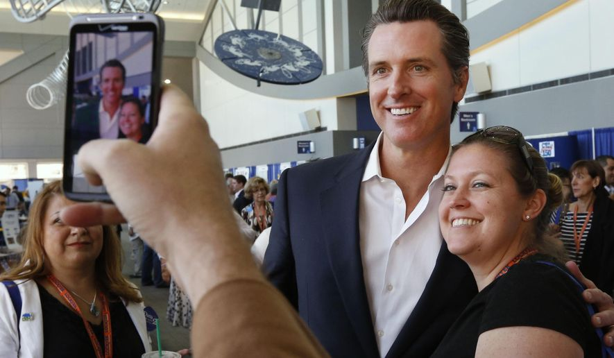 FILE -- In this April 12, 2013 file photo, Lt. Gov. Gavin Newsom poses for a photo with Jennifer Siegert, of Huntington Beach, a delegate to the 2013 Democratic State Convention in Sacramento, Calif. Newsom is being challenged for reelection in the November election  by Republican Ron Nehring.(AP Photo/Rich Pedroncelli,file)