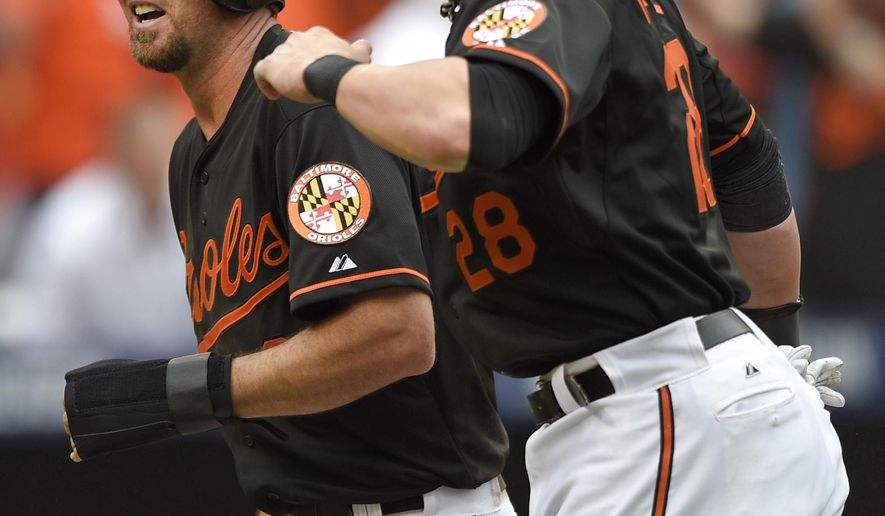 Baltimore Orioles' J.J. Hardy, left, and Steve Pearce celebrate after scoring on a double by Delmon Young during the eighth inning of Game 2 in baseball's AL Division Series against the Detroit Tigers in Baltimore, Friday, Oct. 3, 2014. Baltimore won 7-6. (AP Photo/Nick Wass)