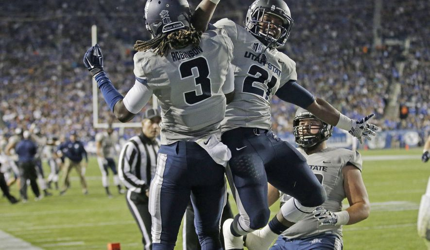 Utah State wide receiver Devonte Robinson (3) celebrates with Utah State running back LaJuan Hunt (21) after catching a touchdown pass in the second quarter during an NCAA college football game  against Brigham Young Friday, Oct. 3, 2014, in Provo, Utah. Utah State won 35-20.  (AP Photo/Rick Bowmer)