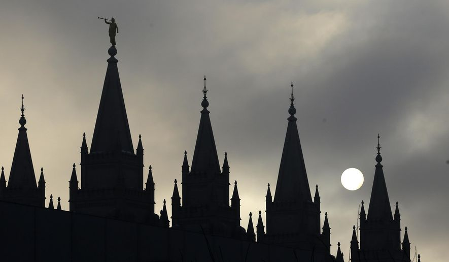 In this Feb. 6, 2013, file photo, the angel Moroni statue, silhouetted against a cloud-covered sky, sits atop the Salt Lake Temple, in Temple Square, in Salt Lake City. (AP Photo/Rick Bowmer, File)